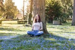 Mujer que se sienta en un prado de la flor de la primavera Imagenes de archivo