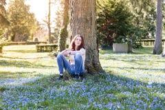 Mujer que se sienta en un prado de la flor de la primavera Fotos de archivo