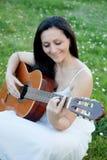 Mujer que se sienta en un prado florecido que toca la guitarra Imágenes de archivo libres de regalías