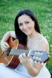 Mujer que se sienta en un prado florecido que toca la guitarra Foto de archivo libre de regalías