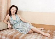 Mujer que se sienta en un sofá fotografía de archivo libre de regalías