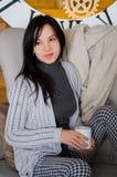 Mujer que se sienta en un sofá Imágenes de archivo libres de regalías