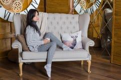 Mujer que se sienta en un sofá Foto de archivo
