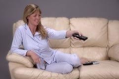 Mujer que se sienta en un sofá que sostiene un control remoto para una TV Foto de archivo