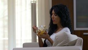 Mujer que se sienta en un sofá que ve la TV y que come la ensalada de fruta que desayuna sano almacen de video