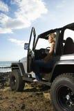Mujer que se sienta en un SUV en la playa Fotos de archivo libres de regalías