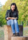 Mujer que se sienta en un tocón de árbol Imágenes de archivo libres de regalías