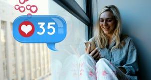 Mujer que se sienta en un travesaño de la ventana que mecanografía en su teléfono 4k almacen de metraje de vídeo