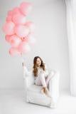 Mujer que se sienta en una butaca y que sostiene un manojo de globos rosados Foto de archivo