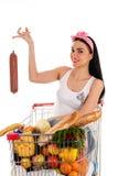 Mujer que se sienta en una carretilla del supermercado Fotos de archivo