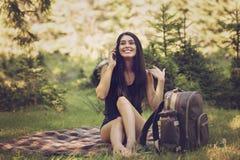 mujer que se sienta en una comida campestre en la naturaleza y las aplicaciones t Fotografía de archivo