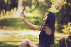 mujer que se sienta en una comida campestre en la naturaleza y las aplicaciones t Imagen de archivo