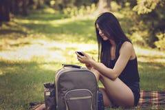 mujer que se sienta en una comida campestre en la naturaleza y las aplicaciones t Imagen de archivo libre de regalías