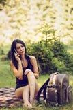 mujer que se sienta en una comida campestre en la naturaleza y las aplicaciones t Fotografía de archivo libre de regalías