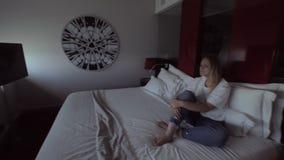 Mujer que se sienta en una habitación y que gira el sistema de abertura automático de la ventana almacen de video