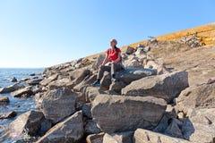 Mujer que se sienta en una piedra al lado de la bici de montaña fotografía de archivo