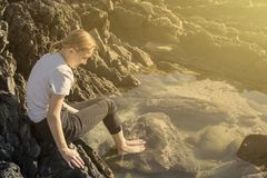 Mujer que se sienta en una piscina de la roca en la salida del sol imágenes de archivo libres de regalías
