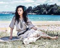 Mujer que se sienta en una playa Fotografía de archivo libre de regalías