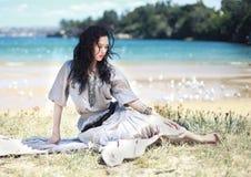 Mujer que se sienta en una playa Fotos de archivo libres de regalías