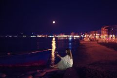 Mujer que se sienta en una playa en la noche debajo de la Luna Llena, aumentando un vidrio de vino Durres, Albania imagen de archivo libre de regalías
