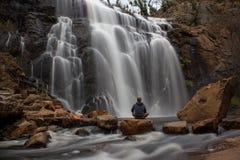 mujer que se sienta en una roca delante de Mackenzie Falls fotografía de archivo libre de regalías