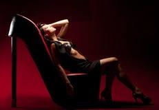 Mujer que se sienta en una silla Imágenes de archivo libres de regalías