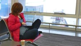Mujer que se sienta en una silla con el cuaderno