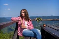 Mujer que se sienta en una tabla en las montañas Fotografía de archivo