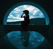 Mujer que se sienta en una ventana foto de archivo libre de regalías
