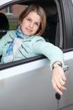 Mujer que se sienta en vehículo de pista con clave del coche Foto de archivo