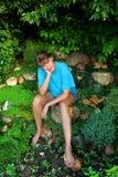 Mujer que se sienta entre las plantas en el jardín Fotos de archivo libres de regalías