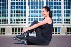 Mujer que se sienta feliz en patines en línea Fotografía de archivo