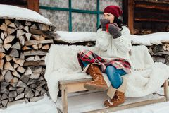 Mujer que se sienta fuera de una cabaña que disfruta de un día nevoso en sus la propio Foto de archivo