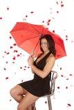Mujer que se sienta lloviendo rosas Imagen de archivo