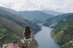 Mujer que se sienta mirando paisaje Depósito y montañas imagenes de archivo