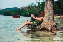 Mujer que se sienta para arriba contra árbol en la playa tropical Imagen de archivo libre de regalías