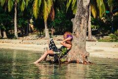 Mujer que se sienta para arriba contra árbol en la playa tropical Fotografía de archivo libre de regalías