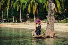 Mujer que se sienta para arriba contra árbol en la playa tropical Fotos de archivo