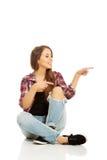 Mujer que se sienta a piernas cruzadas Foto de archivo