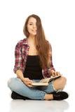 Mujer que se sienta a piernas cruzadas Imágenes de archivo libres de regalías