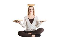 Mujer que se sienta a piernas cruzadas sosteniendo el libro en la cabeza Foto de archivo libre de regalías