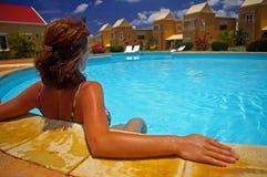 Mujer que se sienta por el borde de la piscina Fotos de archivo libres de regalías