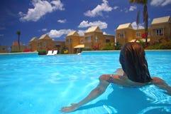 Mujer que se sienta por el borde de la piscina Fotografía de archivo