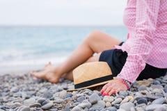 Mujer que se sienta por el mar Imagenes de archivo