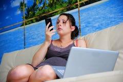 Mujer que se sienta por el ordenador Fotos de archivo