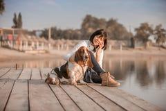 Mujer que se sienta por el río con su perro y que habla en el teléfono imágenes de archivo libres de regalías