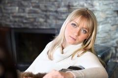 Mujer que se sienta por la chimenea Imagenes de archivo