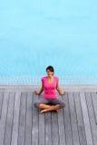 Mujer que se sienta por la piscina Fotos de archivo libres de regalías