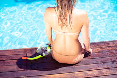 Mujer que se sienta por la piscina con un tubo respirador Imagen de archivo