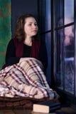 Mujer que se sienta por la ventana Imagen de archivo libre de regalías